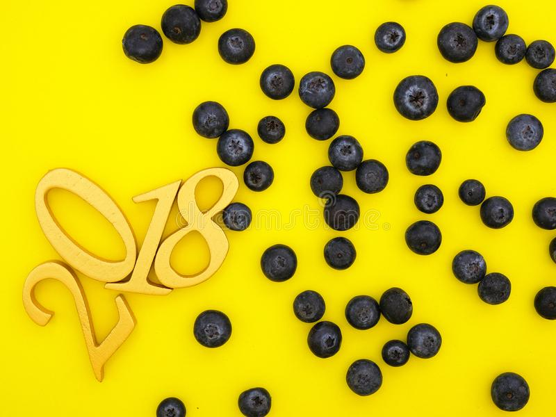 New Year 2018 Banner. A new year 2018 banner in gold and random blueberries pattern on bright yellow paper background royalty free stock image