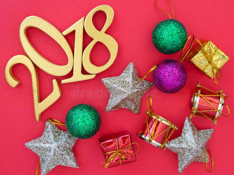 New Year 2018 Banner. A new year 2018 banner in gold and Christmas ornaments on bright red background royalty free stock image