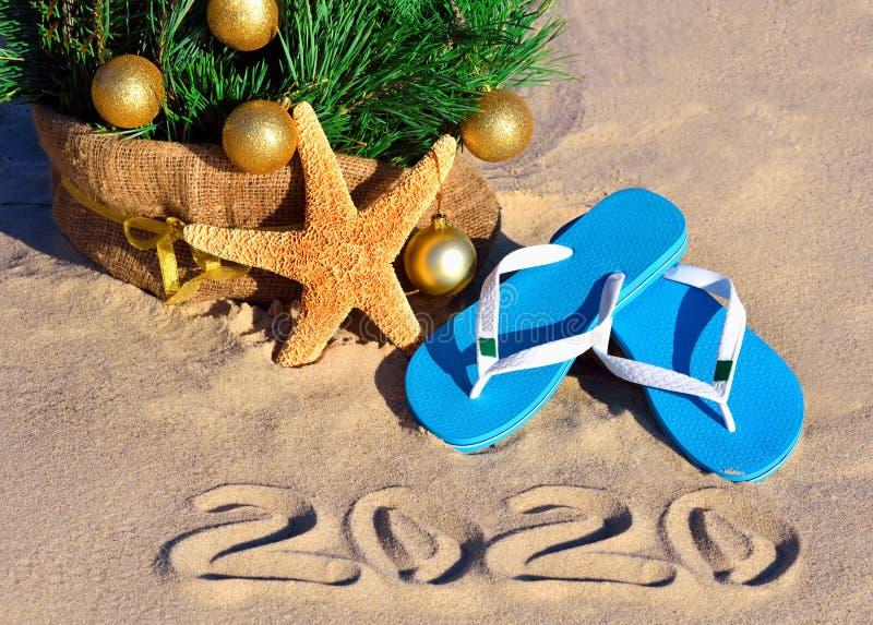 New Year 2020 on the beach 圣诞树,海星和拖鞋 免版税库存照片