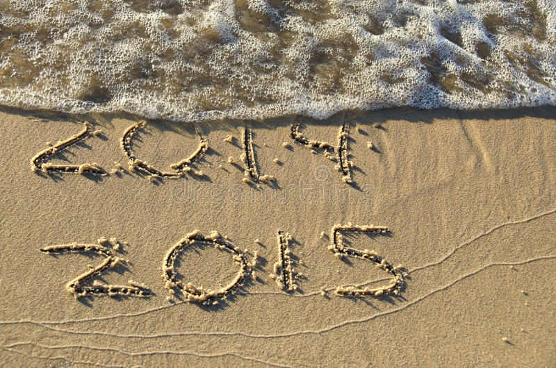 New Year 2015 on beach. New year fro 2015 written in beach sand with foamy surf royalty free stock photos