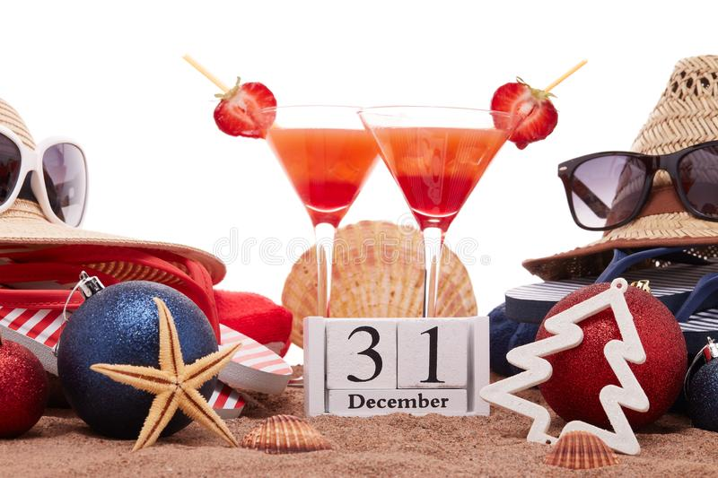 New Year beach holidays. Beach accessories flip flops, straw hats, seashells, sand, sunglasses, two glasses of cocktail, christmas ornaments on white background royalty free stock photos