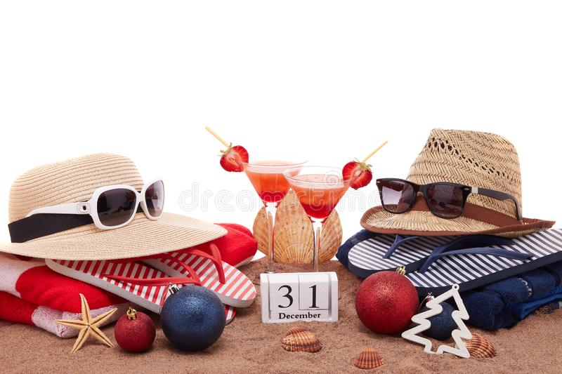 New Year beach holidays. Beach accessories flip flops, straw hats, seashells, sand, sunglasses, two glasses of cocktail, christmas ornaments on white background royalty free stock photo