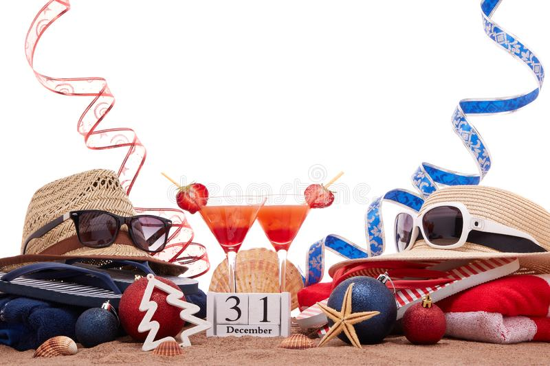 New Year beach holidays. Beach accessories flip flops, straw hats, seashells, sand, sunglasses, two glasses of cocktail, christmas ornaments on white background stock photo