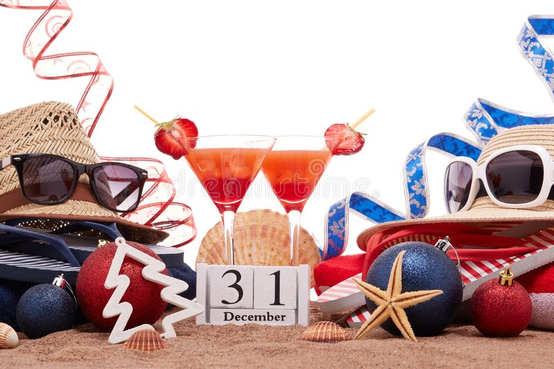 New Year beach holidays. Beach accessories flip flops, straw hats, seashells, sand, sunglasses, two glasses of cocktail, christmas ornaments on white background royalty free stock image