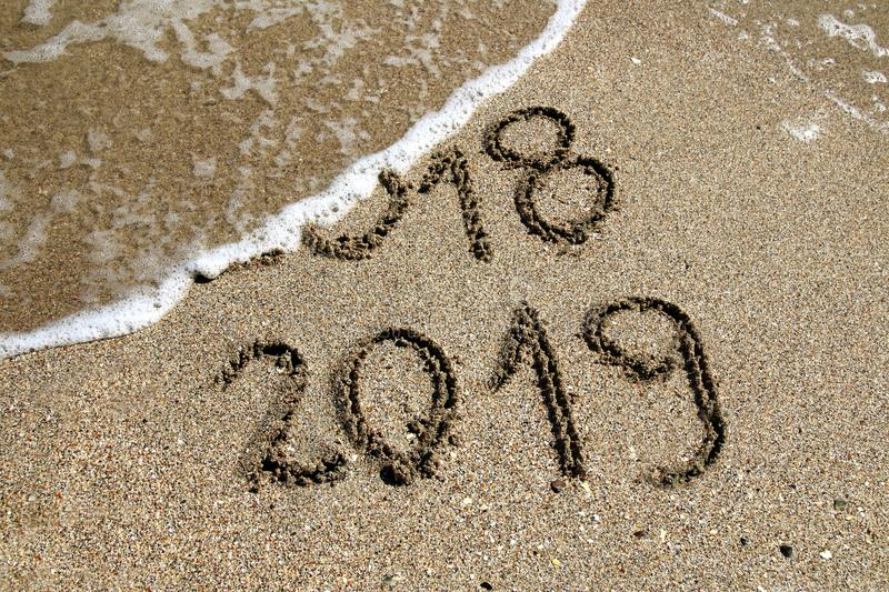 New Year 2019. 2018 and new year 2019 on a beach sand with wave royalty free stock image