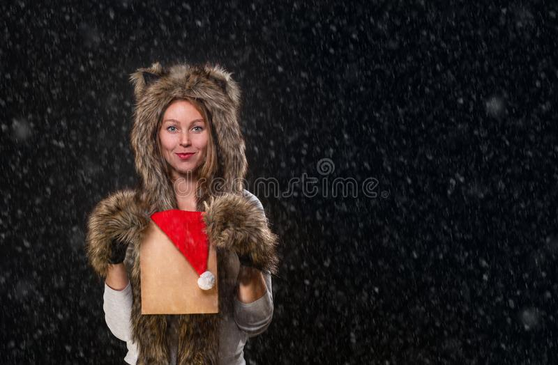 New Year. A beautiful young woman, in a fur hat with ears, and woolly mittens, smiling and holding a package with a Christmas hat royalty free stock photography