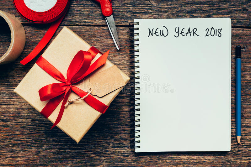 New Year 2018 on blank paper note book on wood table background. stock photography