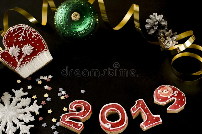 New Year card on black background gingerbread red numbers 2019 with multi-colored stars, gold streamer, red mitten. White snowflake and green christmas toy stock photography