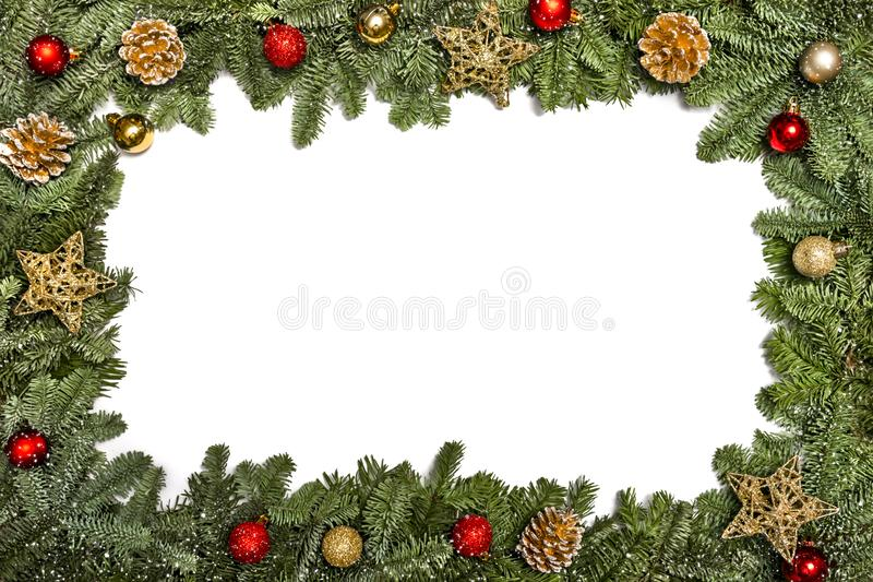 New Year card. Christmas greetings. Frame with New Year`s decoration, Christmas tree branches, golden cones, golden stars and red. Balls on a white background stock photos