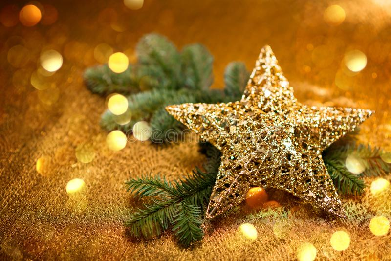 New Year card. Christmas greetings. Golden decorative star with Christmas tree branches, on golden background. stock photo