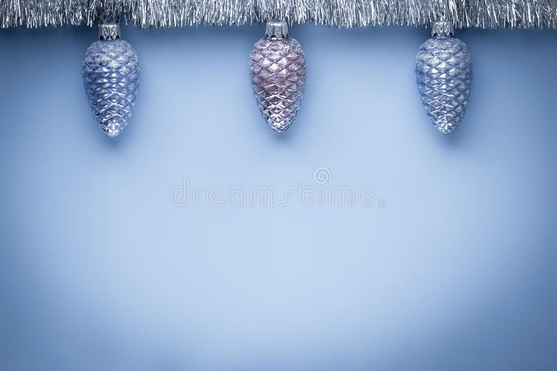 New Year card. Decoration design. Copy space. Top view. Christmas background, mockup. Blue pattern with festive cones and silver g. Arland. Holiday banner royalty free stock photography