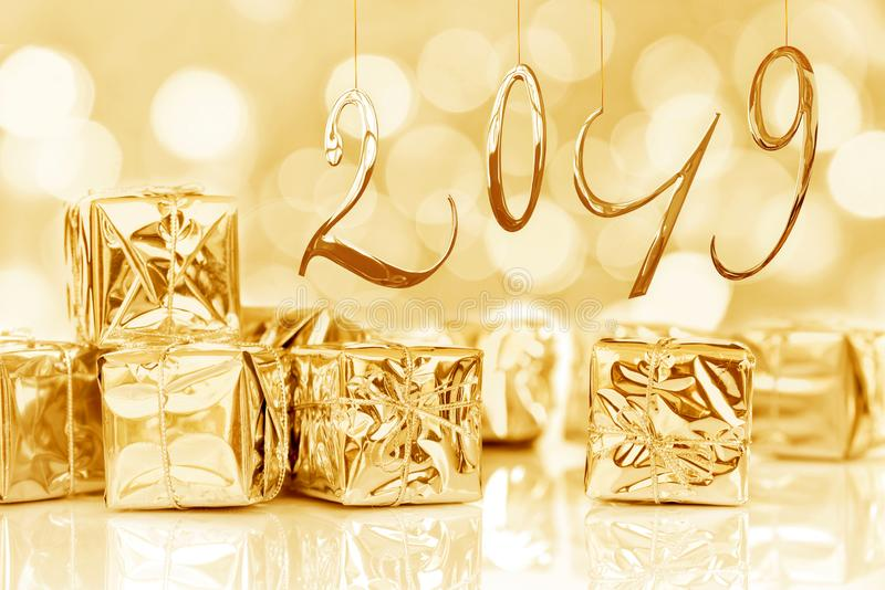 2019 new year card, Small Christmas gifts in shiny golden paper, bokeh background royalty free stock photo