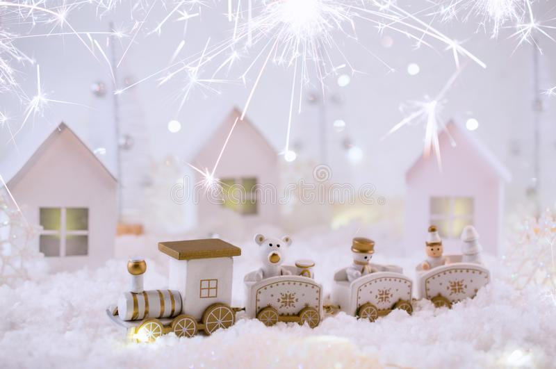 New Year card with toy train in a fairy village on winter background with snow and lights. Party with bengal lights. Magic and fai royalty free stock photo