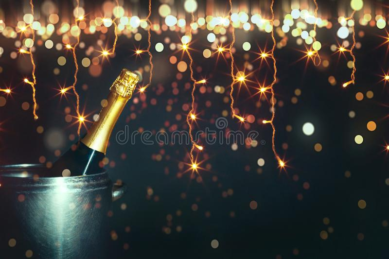 New Year 2019 Celebration Concept. Bottle of champagne on a background of holiday lights with copy-space. New Year 2019 Celebration Concept. Bottle of champagne royalty free stock images