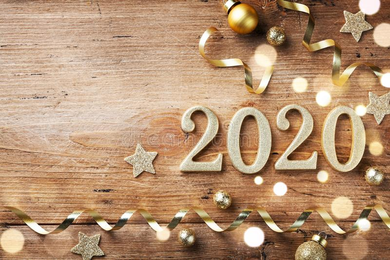 New Year celebration and festive background with golden numbers 2020, confetti stars and Christmas decorations top view stock photography