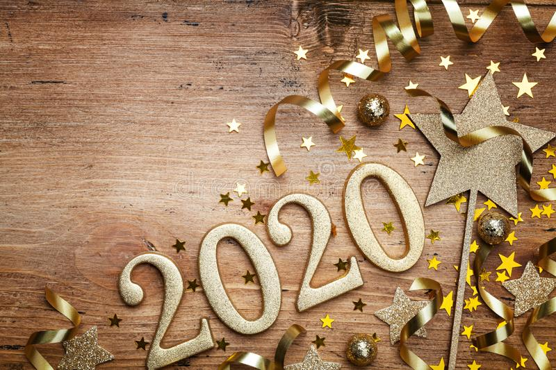 New Year celebration and festive background with golden numbers 2020, confetti stars and Christmas decorations top view. New Year celebration and festive royalty free stock image