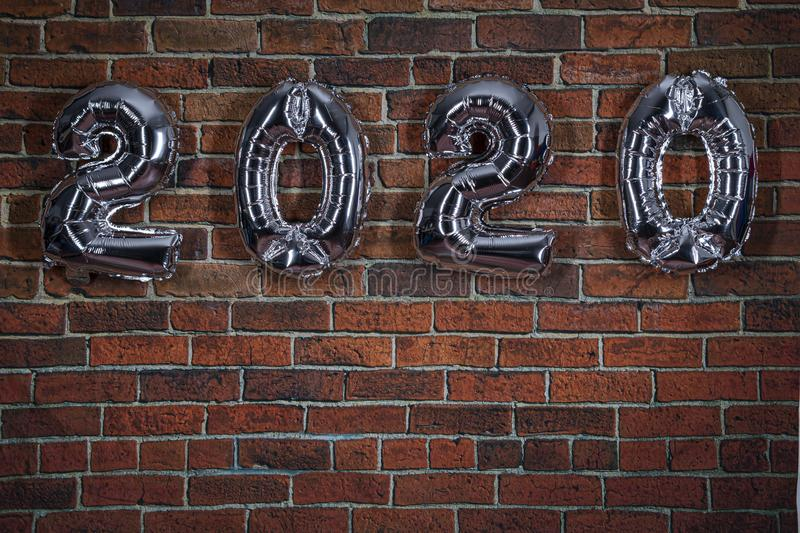 New year 2020 celebration with silver balloons hanging on a brick wall. New Year`s Eve Party Concept stock images
