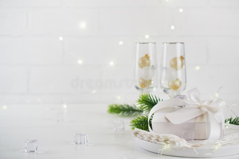 New Year Celebration. Silver Christmas table setting with two champagne glasses on the dinner table and gift box. royalty free stock images