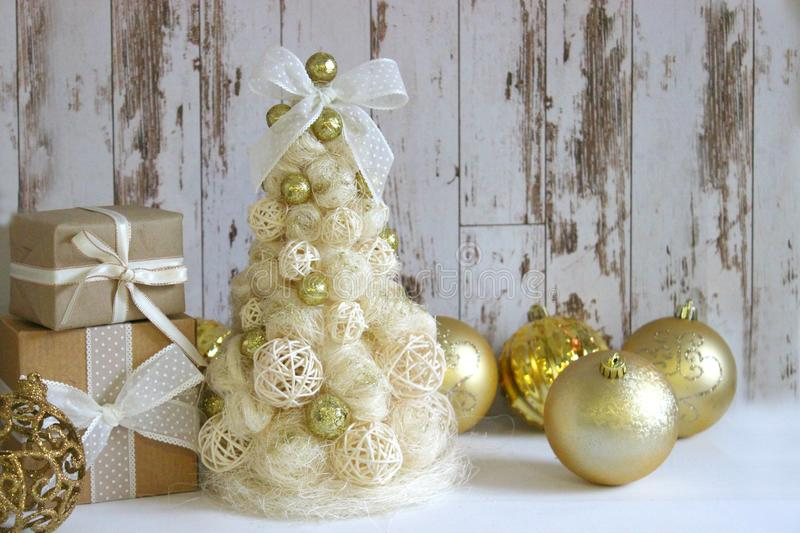 New Year, Christmas background, rustic style. Festive Christmas tree in gold on white wood background and craft boxes tied with sa royalty free stock images