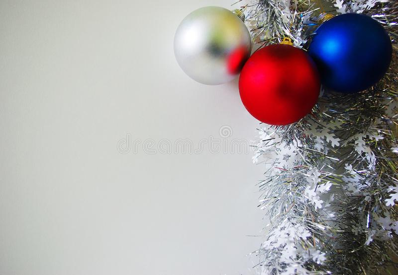New Year Christmas background. Silver tinsel and three multicolored baubles. Holiday decorating concept stock images