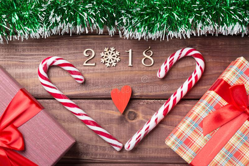 New Year or Christmas card. 2018 wooden decorative figures with heart shaped candy canes, giftboxes and red heart with green spang. Le on wooden background royalty free stock photo