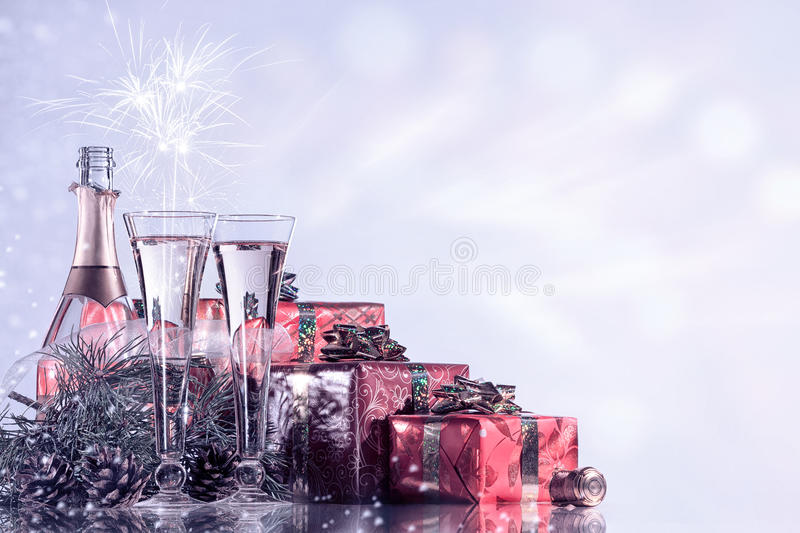 New Year and Christmas celebration. Champagne, two wine glasses, fireworks and gifts on blinking holiday background. stock photo