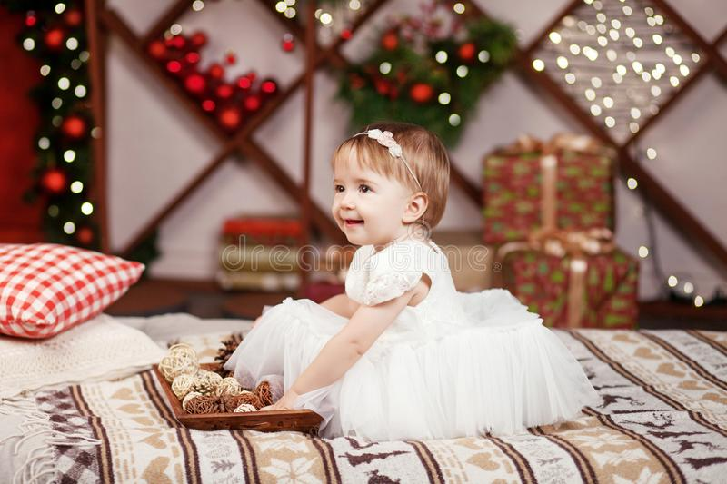 New Year and Christmas celebration concept. Pretty little girl in white dress playing and being happy about christmas tree and. Lights. Winter holidays stock photos