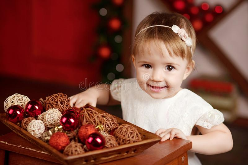 New Year and Christmas celebration concept. Pretty little girl in white dress playing and being happy about christmas tree and stock photos