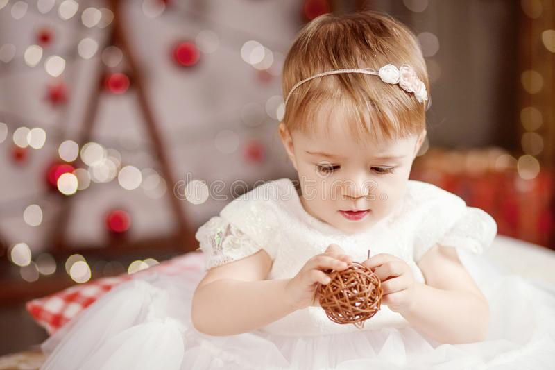 New Year and Christmas celebration concept. Pretty little girl in white dress playing and being happy about christmas tree and stock images