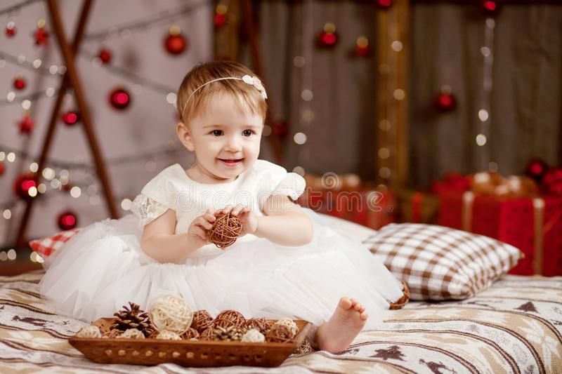 New Year and Christmas celebration concept. Pretty little girl in white dress playing and being happy about christmas tree and royalty free stock photos