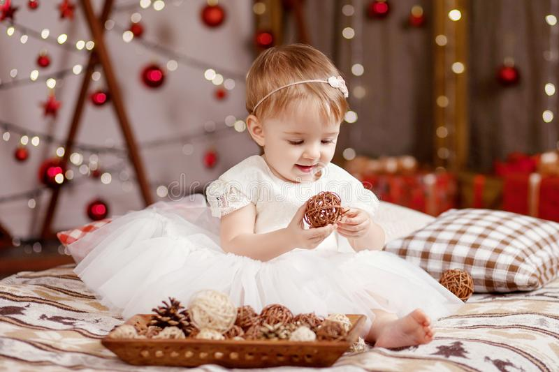 New Year and Christmas celebration concept. Pretty little girl in white dress playing and being happy about christmas tree and. Lights. Winter holidays stock photography