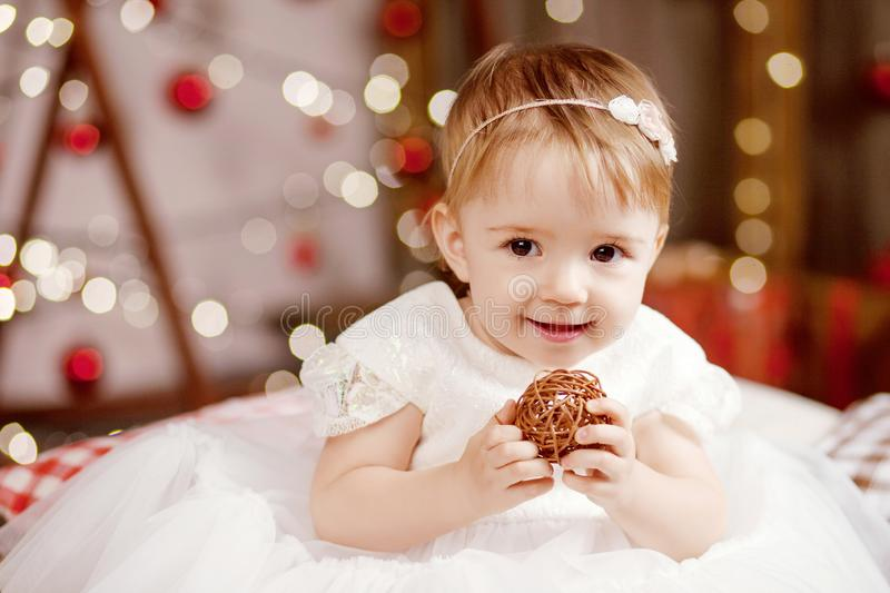 New Year and Christmas celebration concept. Pretty little girl in white dress playing and being happy about christmas tree and. Lights. Winter holidays stock photo