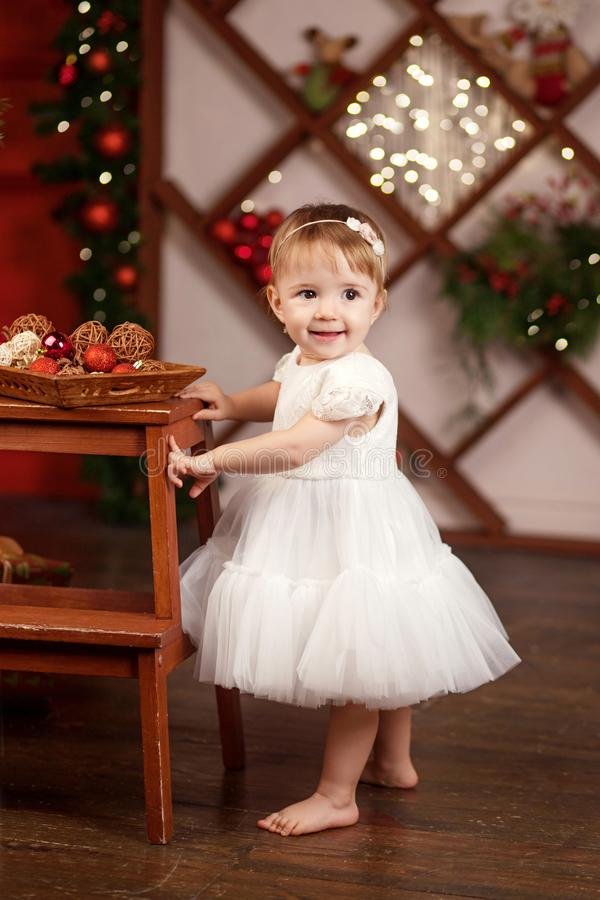 New Year and Christmas celebration concept. Pretty little girl in white dress playing and being happy about christmas tree and stock photo