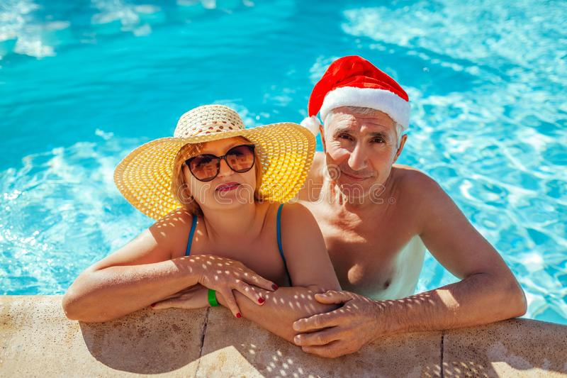New Year and Christmas celebration. Man in Santa`s hat and woman relaxing in swimming pool. Tropical vacation stock photo