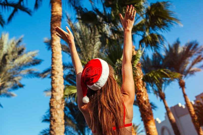 New Year and Christmas celebration. Woman in Santa`s hat and bikini relaxing in swimming pool. Tropical vacation. New Year and Christmas celebration. Woman in stock photo