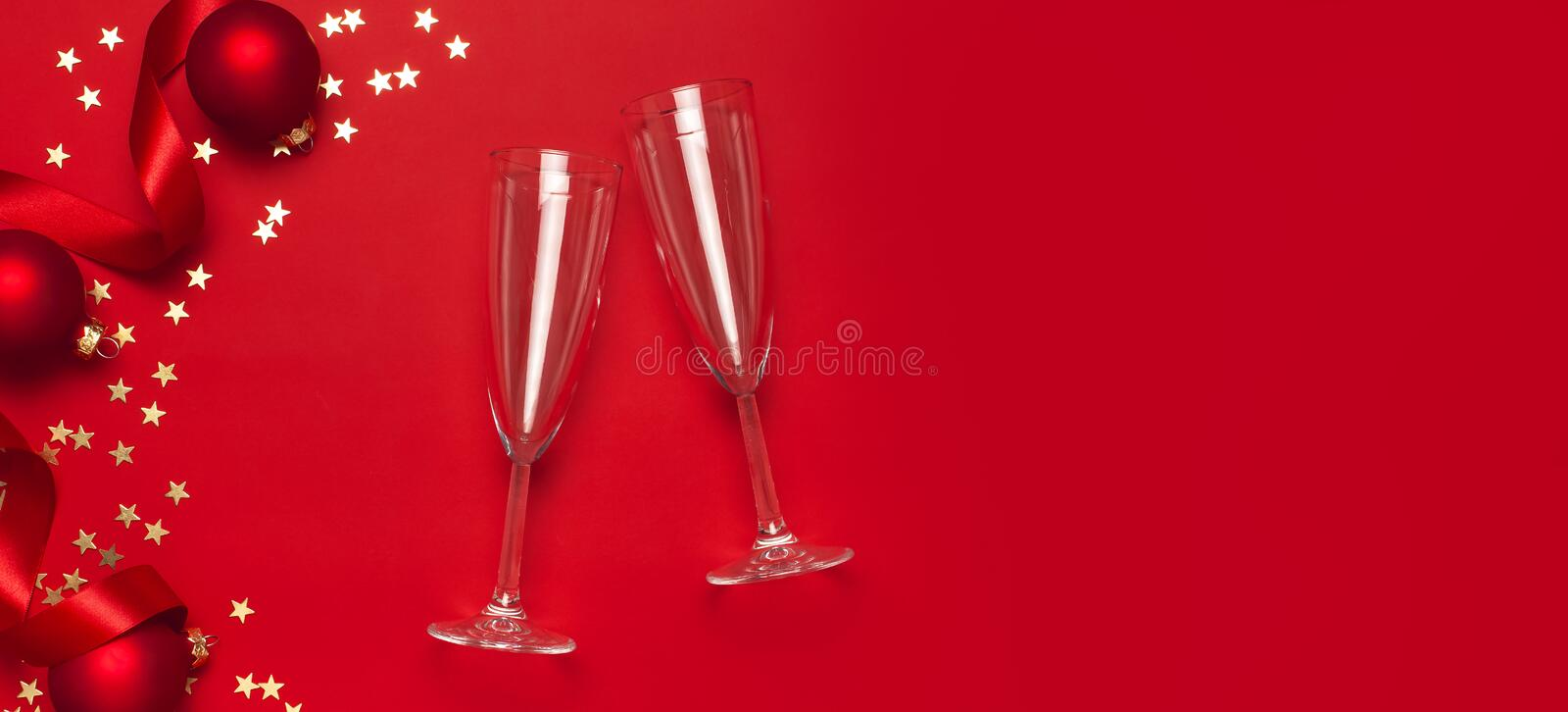 New Year Christmas Champagne glasses, Christmas balls, gold confetti stars on red background top view with copy space. Flat lay royalty free stock images