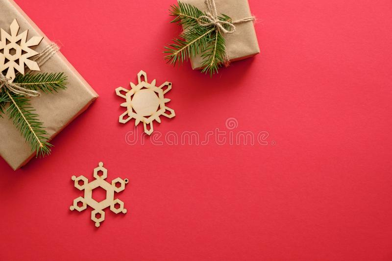 New year or Christmas composition. Presents wrapped kraft paper and fir tree branches, wooden handmade snowflakes decorations on stock photo