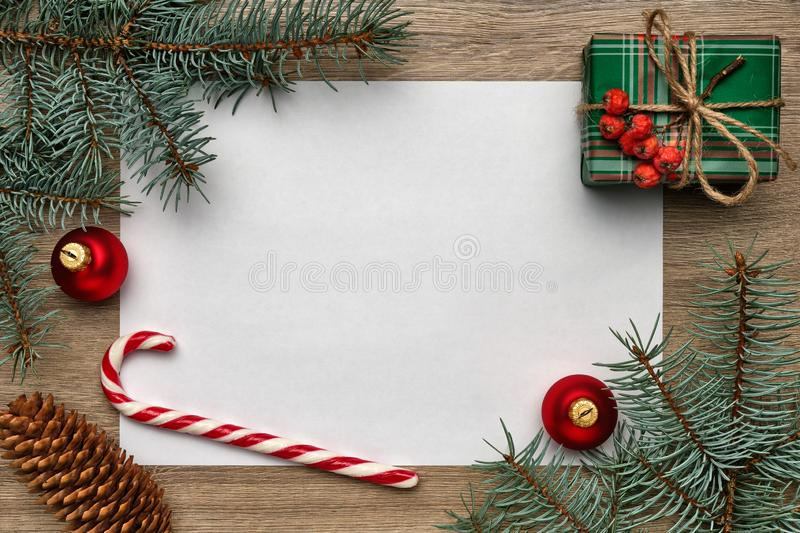 New Year or Christmas composition. White sheet of paper with copy space, gift box, candy cane, Christmas ball and fir royalty free stock photos