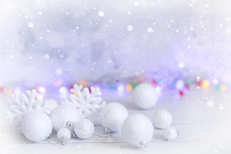 New year or Christmas decorations in silver and white colors with balls, snowflakes and garland bokeh stock images