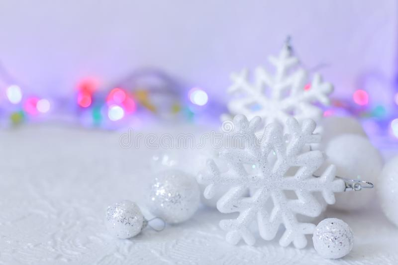 New year or Christmas decorations in silver and white colors with balls, snowflakes and garland bokeh royalty free stock photography