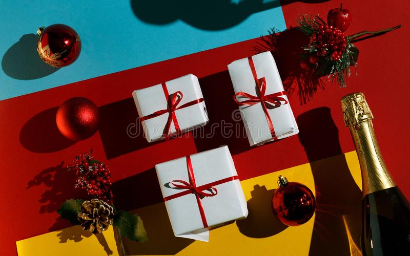 New Year and Christmas 2019 decorative concept. Christmas toys, a bottle of champagne and boxes with gifts in the package on a red stock image