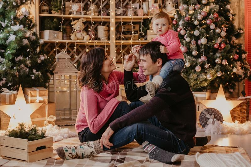 New Year. Christmas. Family. Young parents and their little daughter in Santa hats are spending time together near the Xmas tree. At home stock photos