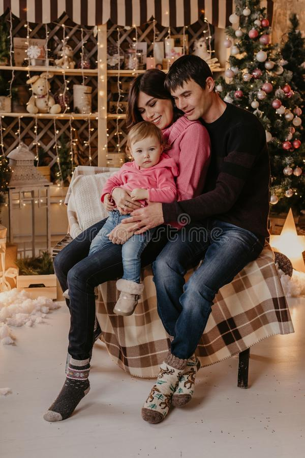 New Year. Christmas. Family. Young parents and their little daughter in Santa hats are spending time together near the Xmas tree. At home royalty free stock images