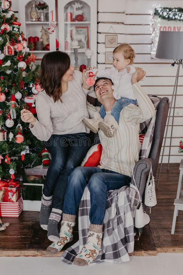 New Year. Christmas. Family. Young parents and their little daughter in Santa hats are spending time together near the Xmas tree. At home stock photo