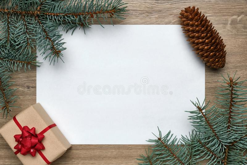 New Year or Christmas festive background. White sheet of paper with copy space, gift box and Christmas tree branches on stock photos