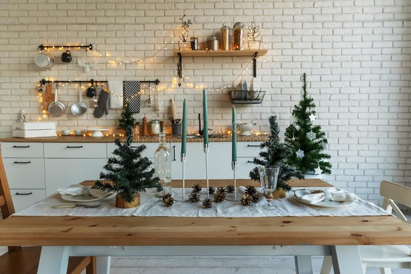 New Year and Christmas 2018. Festive kitchen in Christmas decorations. Candles, spruce branches, wooden stands, table royalty free stock images