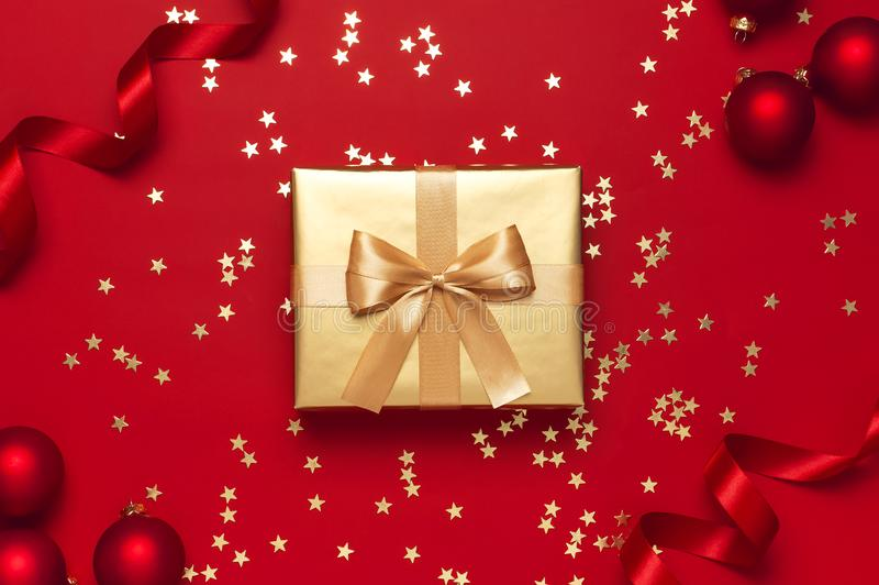 New Year Christmas golden presents with ribbon, Christmas balls, gold confetti stars on red background top view. Flat lay Xmas stock photo