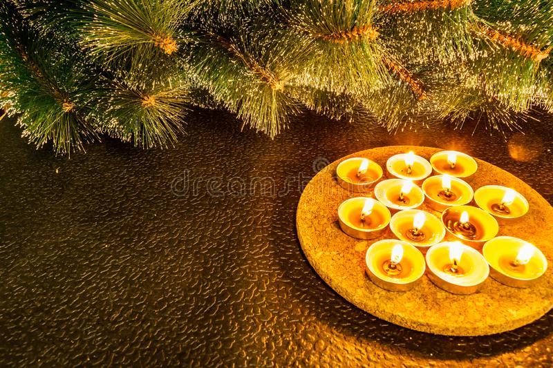 New year and Christmas, green artificial pine on a black background in the light of wax candles. Yellow warm homely touches, the i stock photo