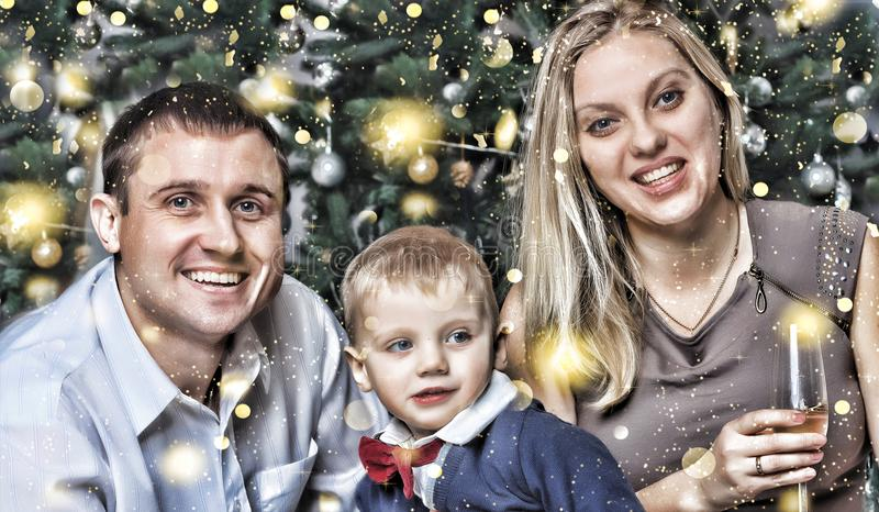 New Year Christmas. Happy young family with a small son happily smiling meets the new year at home. Christmas tree, decorations an stock images