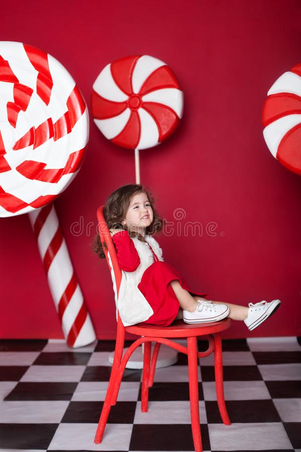New Year 2020! Christmas, holidays and childhood concept. Merry Christmas, happy holidays! Little curly girl is sitting on chair w royalty free stock photography